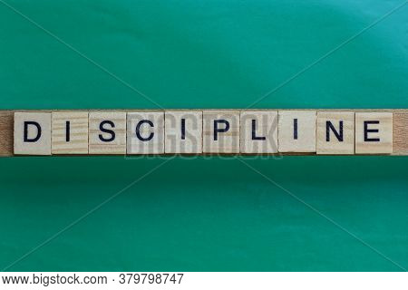 Gray Word Discipline Made Of Wooden Square Letters On Green Background