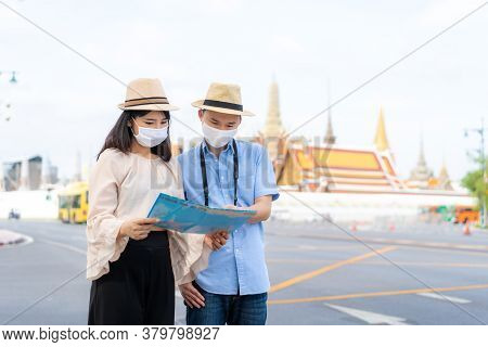 Asian Couple Happy Tourists To Travel Wearing Mask To Protect From Covid-19 On They Holidays And Hol