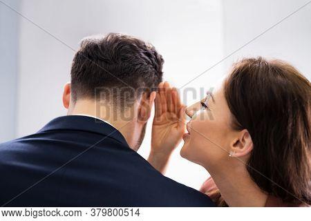 Woman Whispering Gossip In Friend's Ear At Workplace In Office