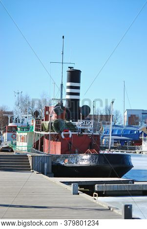 Small Vintage Steamboat In A City Harbor