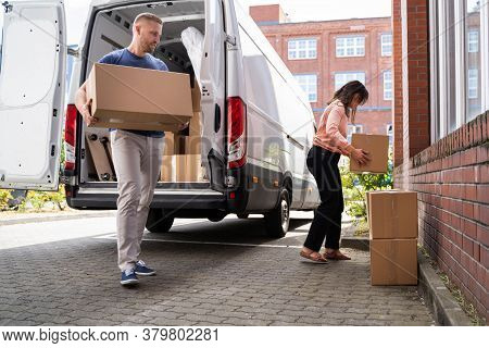 Couple Moving Boxes From Van Or Truck Together Outdoors