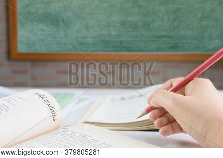 Hand Holding Pencil Over Blurred Textbook On Table In Front Of Blackboard In Classroom
