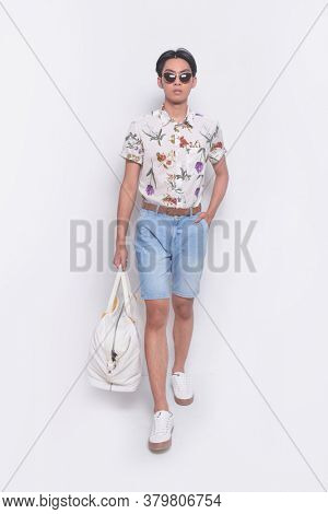 Full body Man casual wearing sunglasses ,new stylish floral, plant ,leaves fern printed sleeve shirts , holding handbag runway in studio