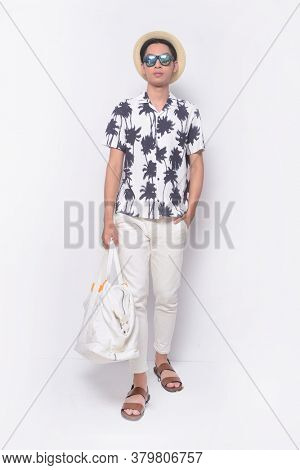 Full body Summer man casual wearing sunglasses,new stylish coconut tree printed t-shirt with white pants and brown shoes with hands holds pocket runway,hat, handbag in studio