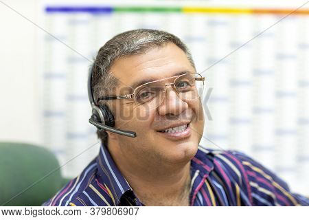 Online Working Concept. Online Working Concept. Smiling Middle Aged Businessman With Headset Looking