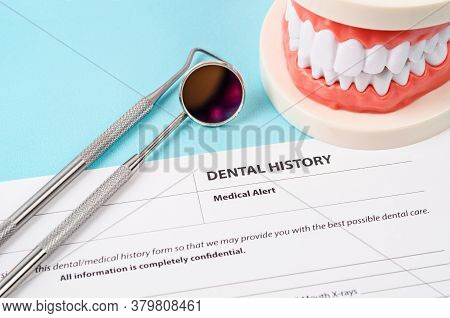 Dental History Form With Model Tooth And Dental Instruments. Dental Health And Teeth Care Concept.