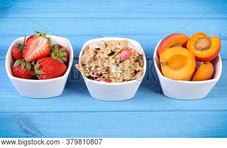 Fresh Strawberries And Apricots, Wheat And Rye Flakes In Glass Bowl On Blue Boards, Concept Of Healt