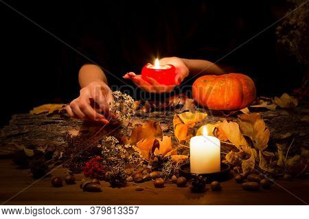 Forest Witch At Work On The Altar. Female Hands With Sharp Red Nails Among Candles, Herbs, Pumpkin,