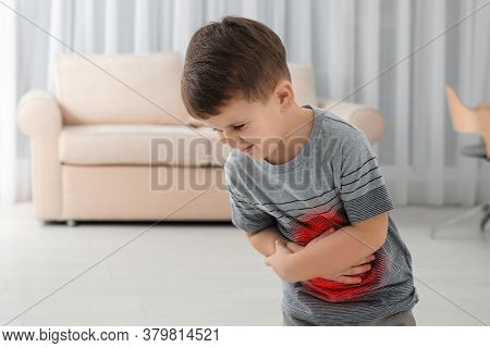Little Boy Suffering From Stomach Pain In Living Room
