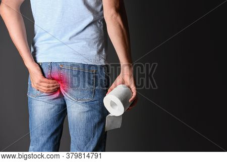 Man With Toilet Paper Suffering From Hemorrhoid On Black Background, Closeup. Space For Text
