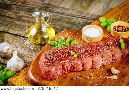 Raw Beef Tenderloin With Herb, Salt And Peppercorn Over Wooden Board.