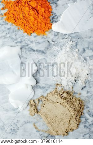 Creamy Texture, Salt, Dry Orange And Light Green Powder Pigmant For Organic Cosmetic On Gray Marble