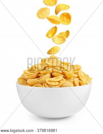 Tasty Crispy Corn Flakes Falling Into Bowl On White Background. Breakfast Cereal