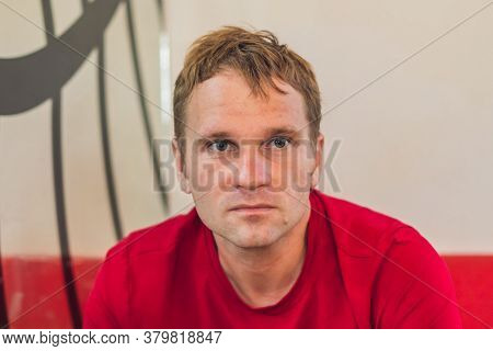 Serious Sad Handsome Blond Man In Casual Style Red T-shirt Sitting, Waiting Someone Or Changes, Thin