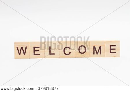 The Word Welcome Is Made Of Wooden Cubes On A White Background. Welcome Text