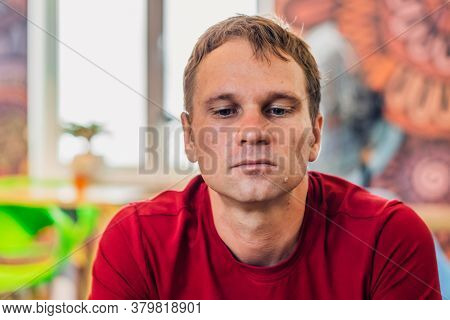 Serious Sad Handsome Blond Man In Casual Style Red T-shirt Sit Look Down, Waiting Someone Or Changes