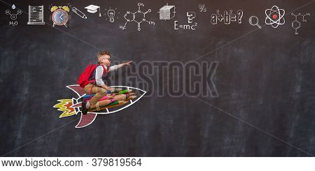 Portrait Of Young Child Sitting On Rocket With Bag. Kid Playing At Home. Child Flying On Drawn Rocke