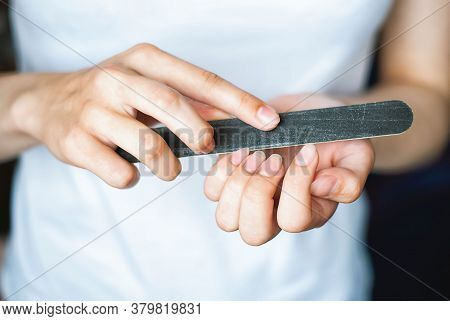 A Young Girl Saws Her Nails With A Black Nail File. Women's Nails And Nail File. Alignment Of The Na