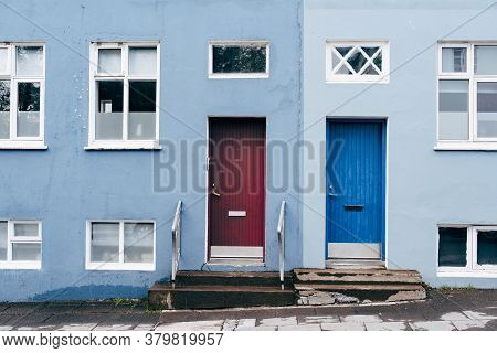 A Two-tone Building In Blue And Light Blue With Two Rectangular Doors In Blue And Burgundy And Windo