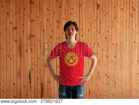 Man Wearing Kyrgyzstan Flag Color Shirt And Standing With Akimbo On The Wooden Wall Background, Red