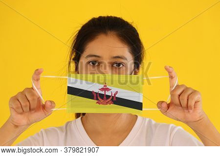 A Woman In White Shirt With Brunei Flag On Hygienic Mask In Her Hand And Lifted Up The Front Face On