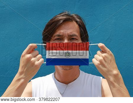 A Man With Paraguay Flag On Hygienic Mask In Her Hand And Lifted Up The Front Face On Blue Backgroun