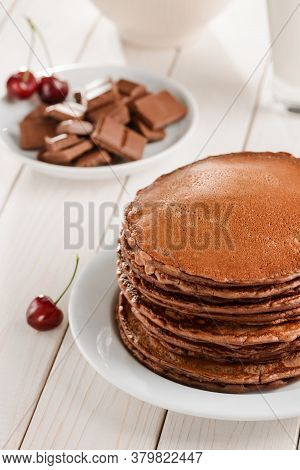 Brown Pancakes, Chocolate And Cherries On White Wooden Table