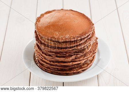 Huge Pile Of Fluffy Brown Pancakes On White Wooden Table