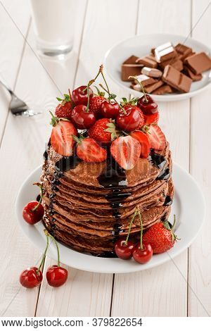 Brown Pancakes With Berries And Chocolate On Wooden Table