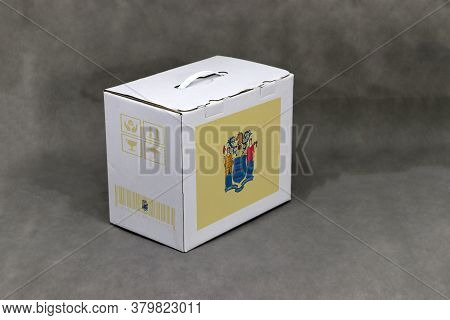 New Jersey Flag On White Box And State Flag Barcode With Fragile Symbol On Grey Background. The Conc