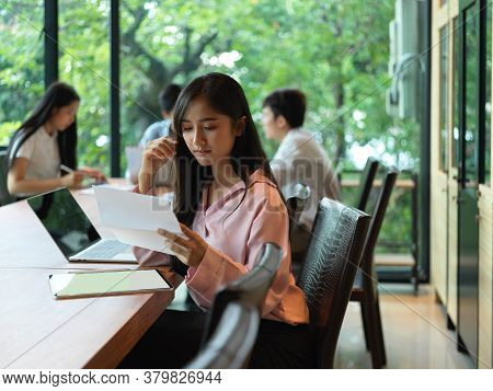 Portrait Of Female Office Worker Reading Informations On Paperwork While Sitting In Co-working Space