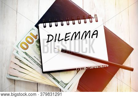 Dilemma Text Written On Notebook With Dollar Bills And Pencil. Financial Concept