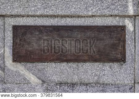 Blank Template Brown Bronze Plaque On Gray Granite Wall. Vintage Background With Copy Space Of The O