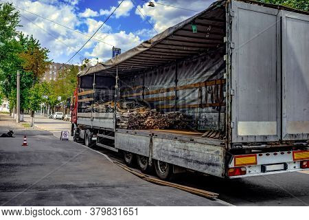 Loading Metal Rods And Cables Into Cargo Wagon Of The Truck On A City Street. Semi-empty Cargo Box O