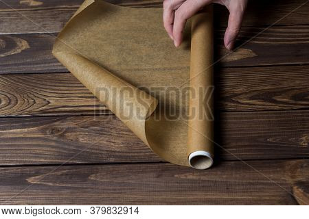 Roll Of Baking Paper On A Wooden Table. Paper For Packaging. Female Hand Rolls A Roll Of Paper.