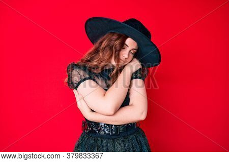 Young beautiful woman wearing witch halloween costume hugging oneself happy and positive, smiling confident. self love and self care