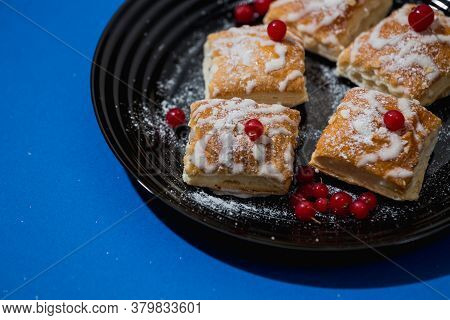 Gourmet French Pastries Decorated With Red Currant Berries In A Black Plate On A Blue Background. Mo