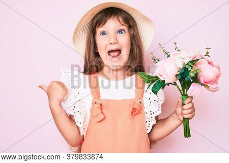 Little caucasian kid girl with long hair holding flower wearing spring hat pointing thumb up to the side smiling happy with open mouth