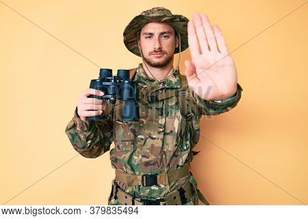 Young caucasian man wearing camouflage army uniform holding binoculars with open hand doing stop sign with serious and confident expression, defense gesture