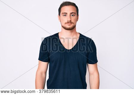 Young handsome man wearing casual clothes with serious expression on face. simple and natural looking at the camera.