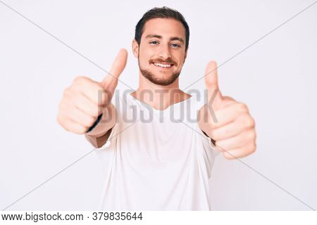 Young handsome man wearing casual white tshirt approving doing positive gesture with hand, thumbs up smiling and happy for success. winner gesture.