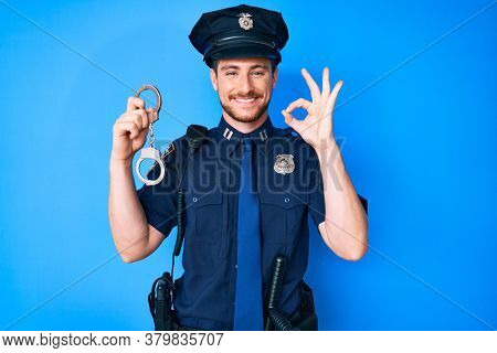 Young caucasian man wearing police uniform holding handcuffs doing ok sign with fingers, smiling friendly gesturing excellent symbol
