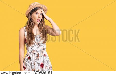 Beautiful caucasian young woman wearing summer hat surprised with hand on head for mistake, remember error. forgot, bad memory concept.