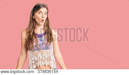 Beautiful caucasian young woman wearing bikini and sunglasses scared and amazed with open mouth for surprise, disbelief face
