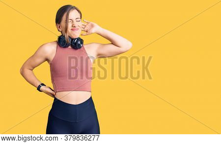 Beautiful caucasian young woman wearing gym clothes and using headphones suffering of neck ache injury, touching neck with hand, muscular pain