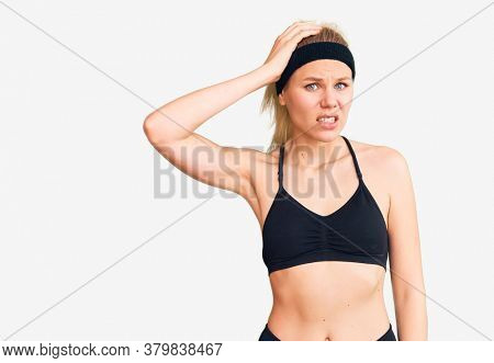 Young beautiful blonde woman wearing sportswear confuse and wonder about question. uncertain with doubt, thinking with hand on head. pensive concept.