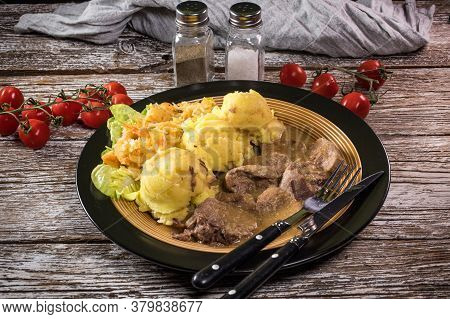 Braised Pork Tongues In Horseradish Sauce Served With Potatoes And Salad.