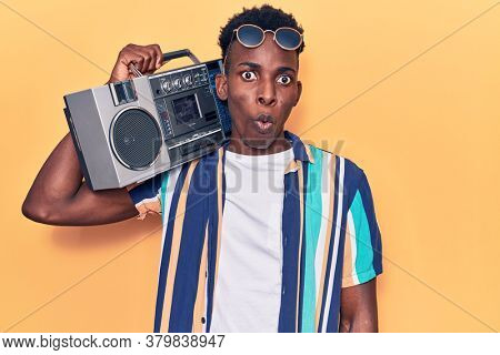 Young african american man holding boombox, listening to music scared and amazed with open mouth for surprise, disbelief face
