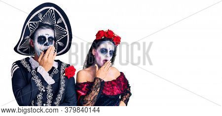 Young couple wearing mexican day of the dead costume over background bored yawning tired covering mouth with hand. restless and sleepiness.