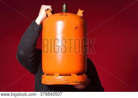 Man Holding A Bottle Of Butane Gas On Red Background